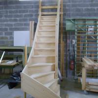 Montage et ajustage escalier en pin en atelier