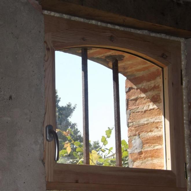 fenêtre cintrée en pin dans une grange sur Aurice